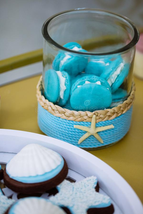 Macaron cookies in a starfish jar on marine thematic candy bar. Blue and white macarons in a starfish jar on marine thematic candy bar, seashell cookies stock photos
