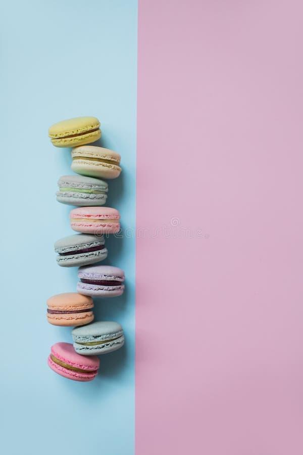 Macaron eller makronkex på pastellfärgad bästa sikt för blå och rosa bakgrund royaltyfri foto