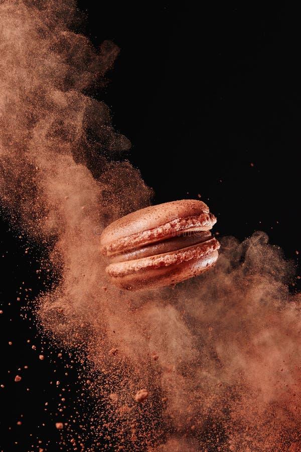 Chocolate Macaron Against Black Background. Macaron explosion. French chocolate macaron with cocoa powder against black background royalty free stock photos