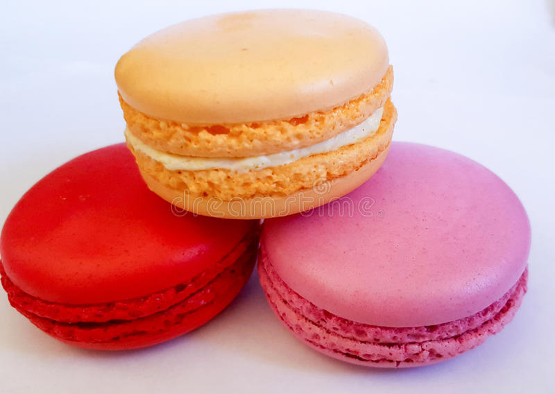 Macaron is a French confection of egg whites, powdered sugar, granulated sugar, ground almonds and food coloring. R. Ed, orange and pink macarons stock images