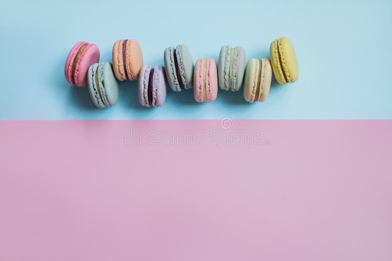 Macaron lub macaroon ciastka na pastelowym tle błękitnym i różowym kosmos kopii zdjęcie stock
