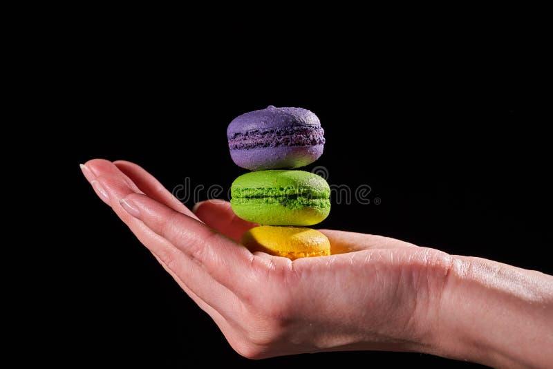 Macaron o macarrones de la torta en la mano de una mujer Aislado en fondo negro fotos de archivo