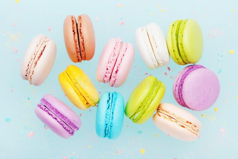 Macaron o macarrones de la torta que vuelan en fondo del pastel de la turquesa Galletas de almendra coloridas en el postre fotografía de archivo