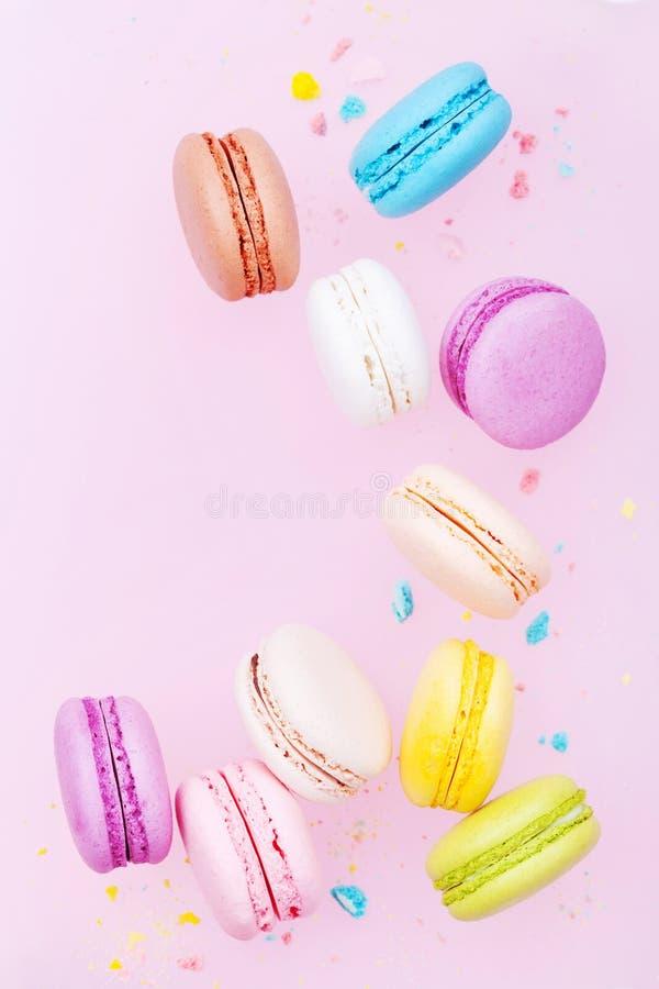 Macaron o maccherone volante del dolce su fondo pastello rosa Biscotti di mandorla variopinti sul dessert immagine stock libera da diritti