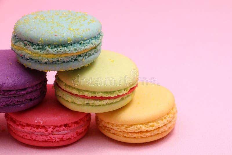 Macaron variopinto o maccherone del dolce del primo piano su fondo rosa dalla vista frontale, biscotti di mandorla variopinti, co fotografia stock libera da diritti