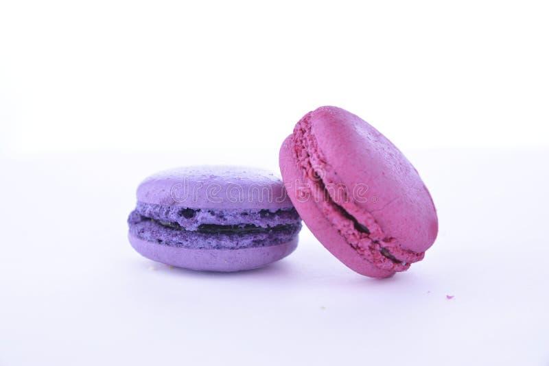 Macaron violet et rose sur un fond blanc, dessert images stock