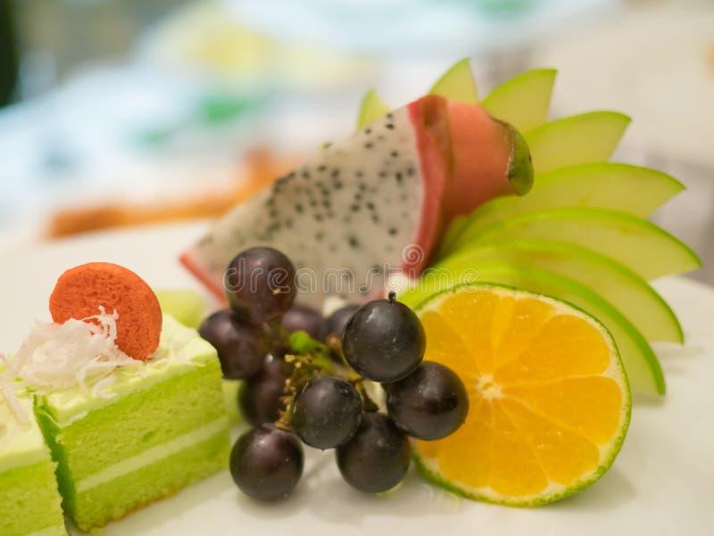 Macaron vuelve a llenar en la torta adornada con las frutas en la placa blanca fotos de archivo libres de regalías