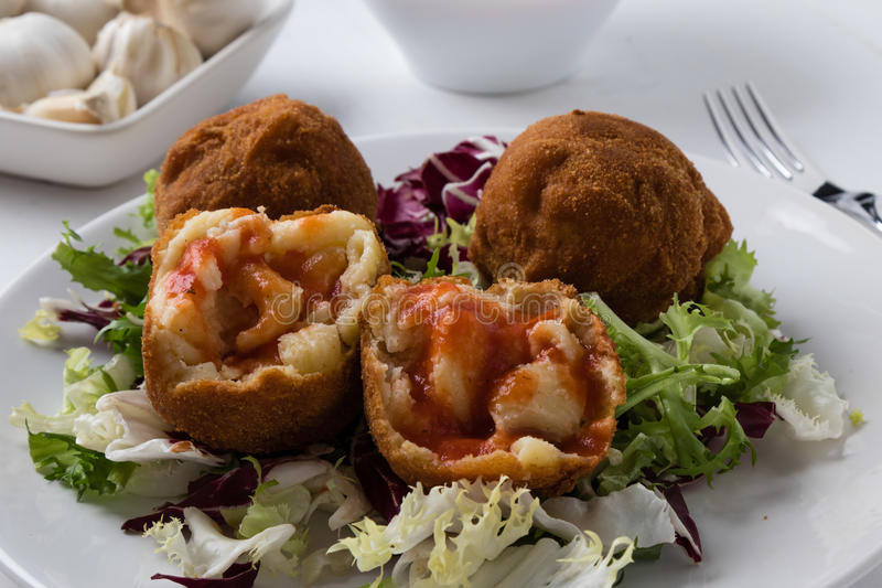 Macaroni and cheese balls. On white plate with salad stock images