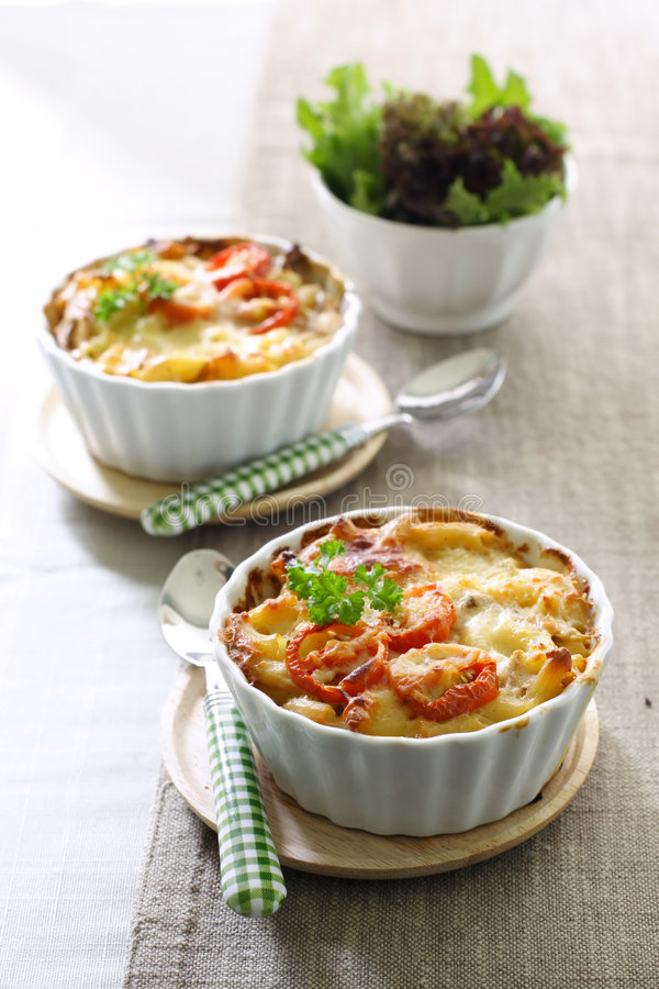 Macaroni and cheese with tomato. Macaroni and cheese served in two ramekin with cherry tomato, and green salad aside royalty free stock images