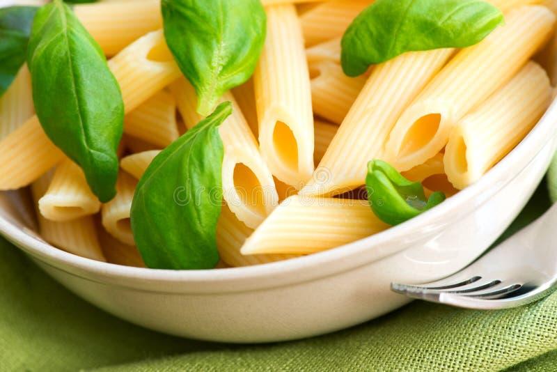 Macaroni en basilicum op dichte omhooggaand van de tbledoek royalty-vrije stock fotografie