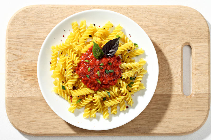 Macaroni fusilli with tomatoes sauce in white ceramic plate on wooden cutting board. stock photos