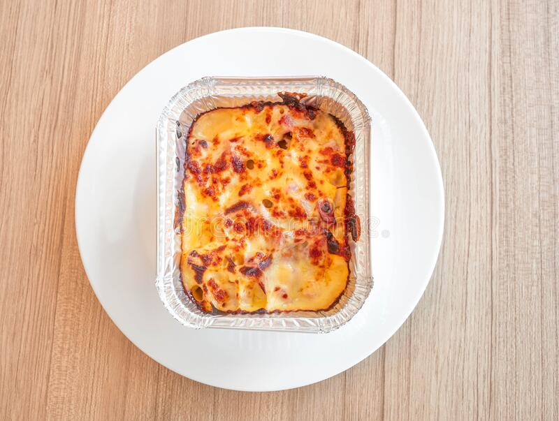 Macaroni with ham and cheese in a baking dish on wooden table. Top view royalty free stock photos