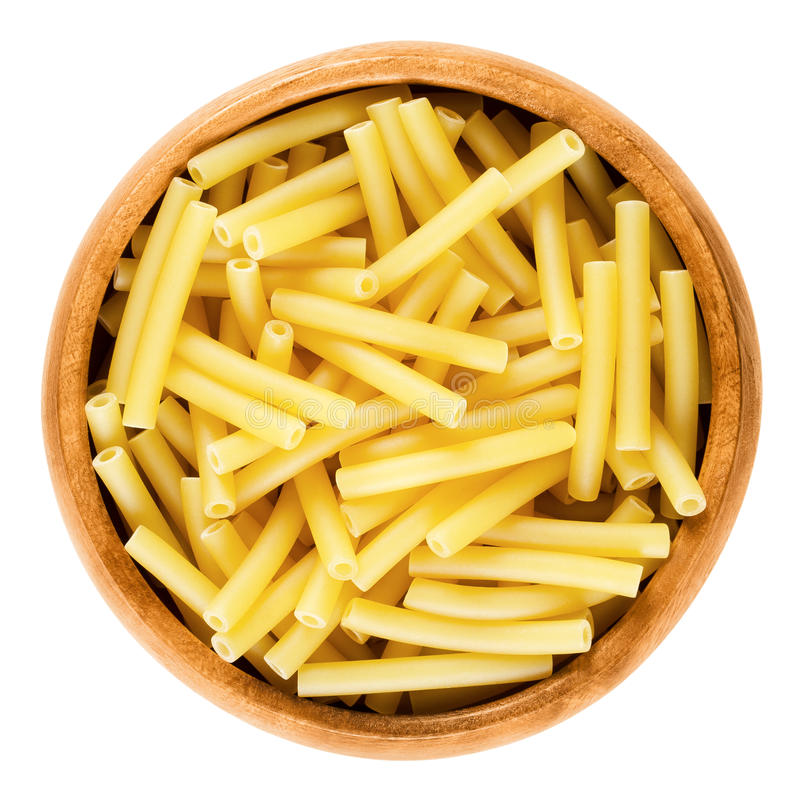 Macaroni pasta in wooden bowl, Italian maccheroni. Short-cut noodles in the shape of narrow tubes. Uncooked dried durum wheat semolina pasta. Isolated macro stock photography