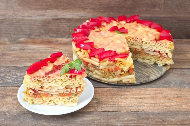 Macaroni pie. Baked macaroni pie with red peppers on wooden stock photography