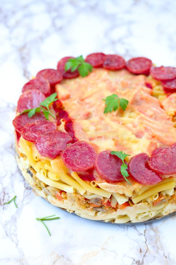 Macaroni pie. Whole baked macaroni pie with cheese and salami royalty free stock images