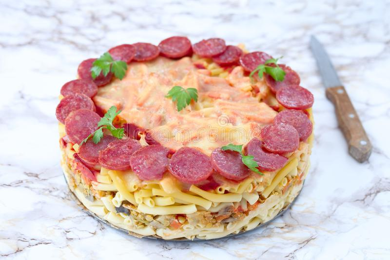 Macaroni pie. Whole baked macaroni pie with cheese and salami royalty free stock image
