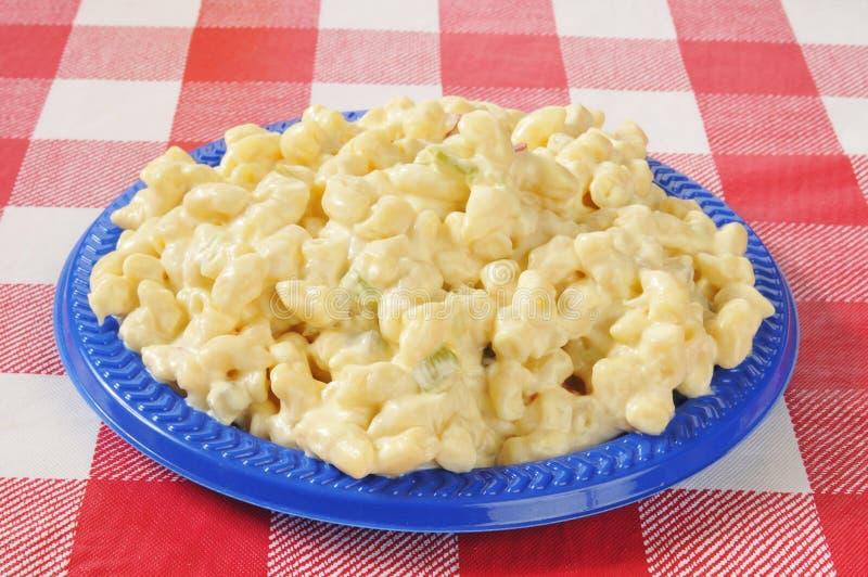 Macaroni salad. A plate of macaroni salad on a picnic table stock photo