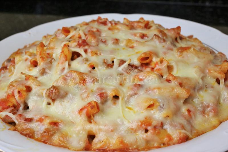 Macaroni with tomato meat and cheese. The food is on a white plate on a black background of a granite table. It is a recipe for homemade cooking very popular stock image