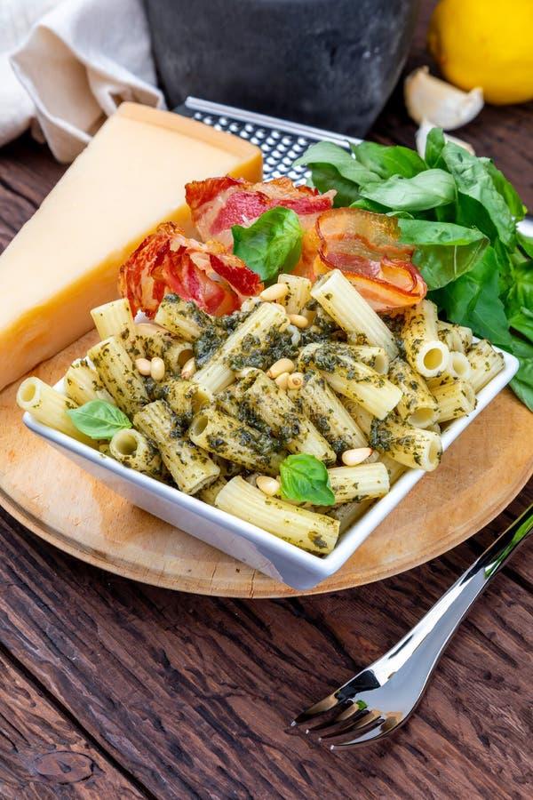 Macaronis avec le rigate de penne de pesto À l'oignon et au lard, fromage, basilic, pignons, ail photos stock