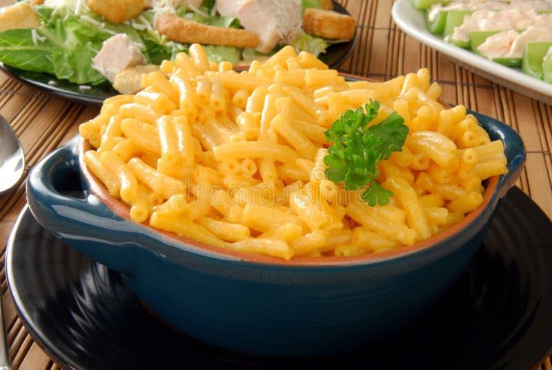 Macaronis et fromage et une salade de César photographie stock