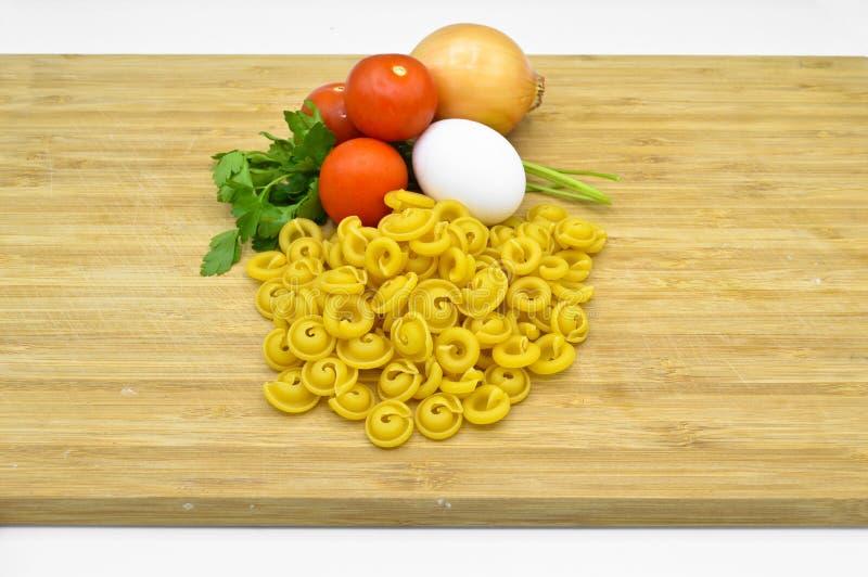 Macaronis, tomates, oeuf et oignon crus et frais images libres de droits