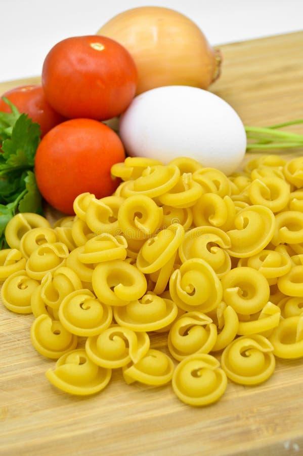 Macaronis, tomates, oeuf et oignon crus et frais images stock
