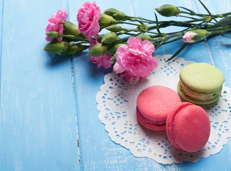 Macarons和花在蓝色颜色表上 免版税图库摄影