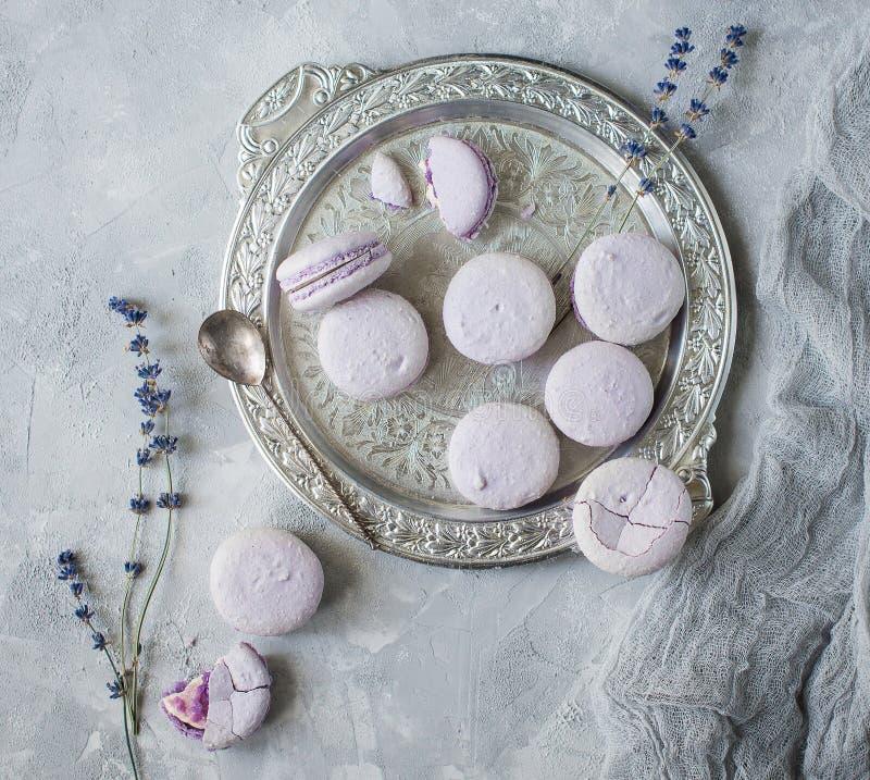 Macarons在碗和在与杯子和淡紫色的桌上 库存照片
