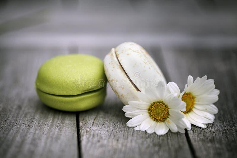 Macarons με τα λουλούδια της Daisy στον αγροτικό ξύλινο πίνακα στοκ εικόνα
