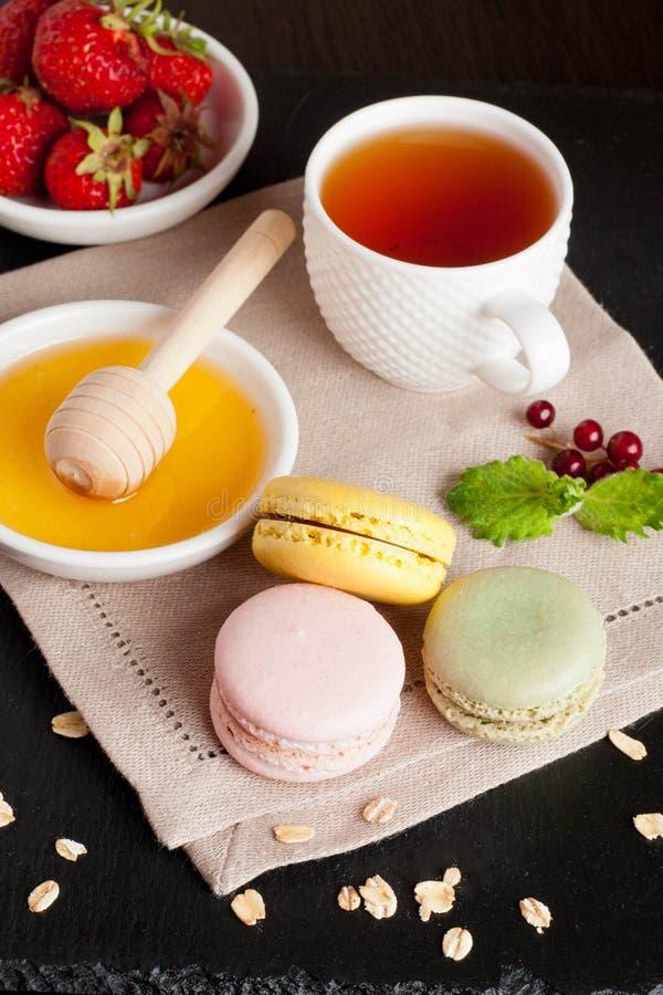 Macarons με το φλυτζάνι του τσαγιού στο μαύρο υπόβαθρο στοκ εικόνα