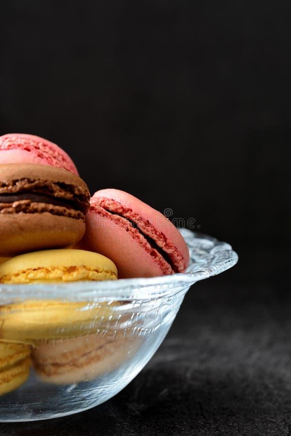 Macarons σε ένα κύπελλο Μαύρη ανασκόπηση στοκ εικόνα με δικαίωμα ελεύθερης χρήσης