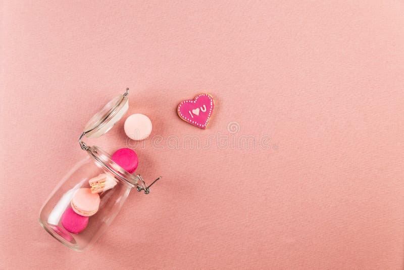Macarons или macaroons француза пинка и мадженты, и я тебя люблю печенье падая из стеклянного опарника Розовый космос предпосылки стоковая фотография rf