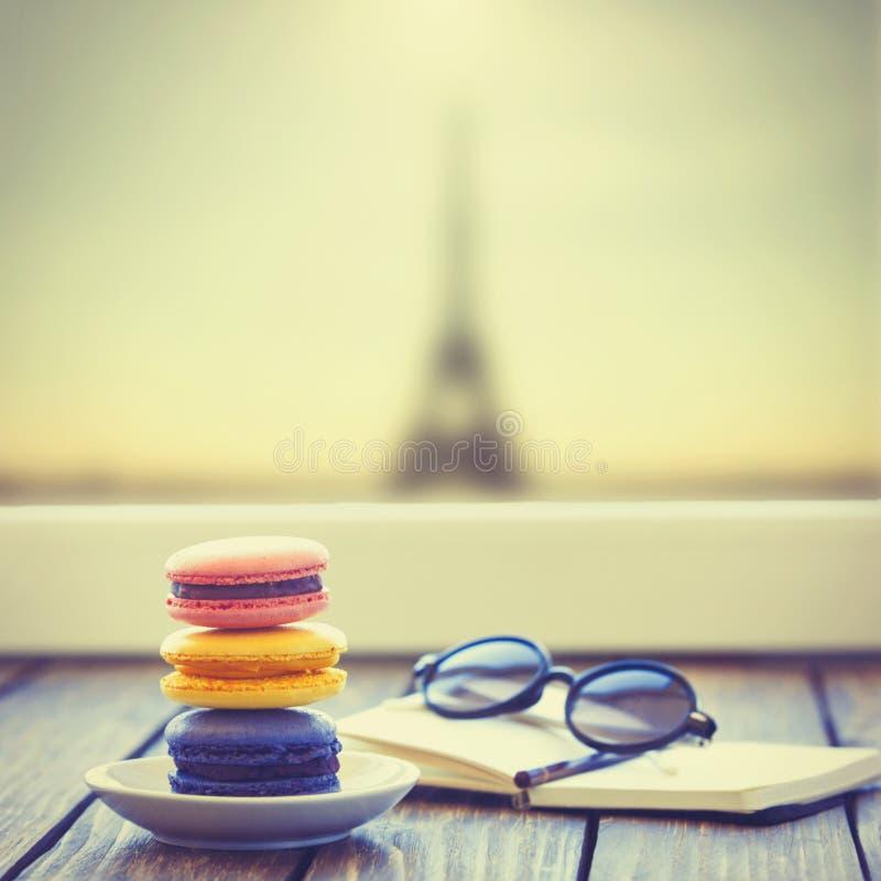 Macarons и меньшая тетрадь с стеклами стоковая фотография rf