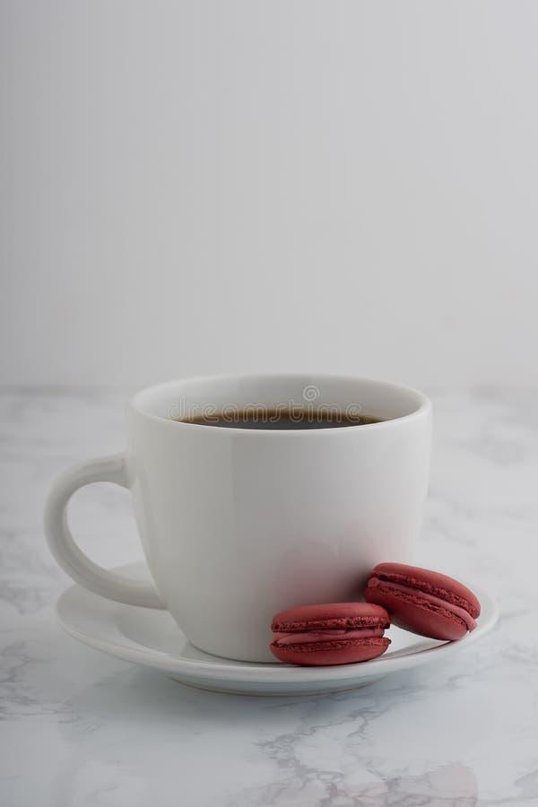 2 macarons шоколада французских с чашкой кофе на белом marb стоковые изображения rf