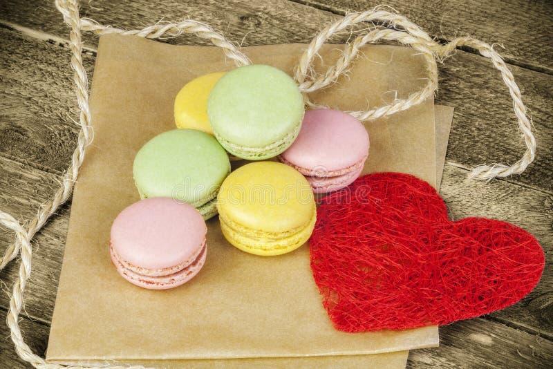 Macarons以在纸近的红色纸心脏的各种各样的颜色 库存图片