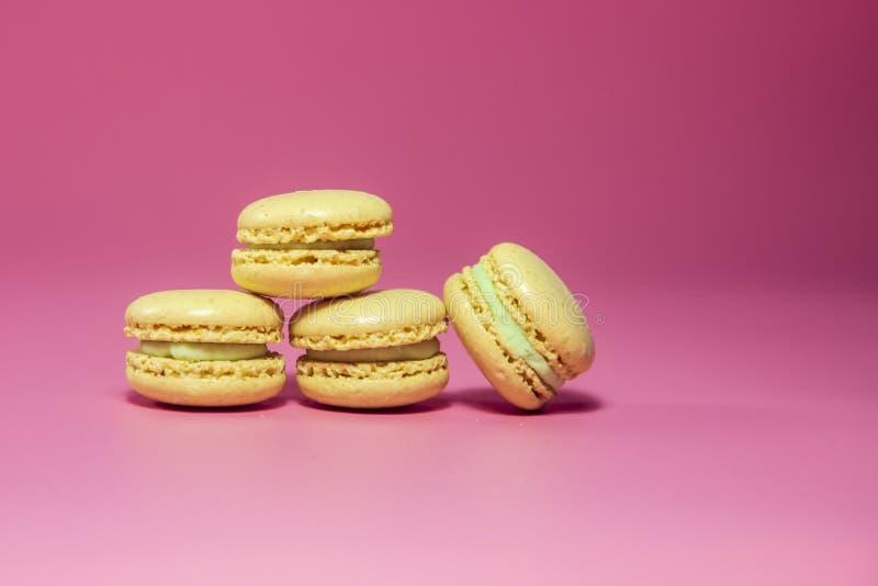 Macarons amarillo Macarons en backgtound rosado fotos de archivo