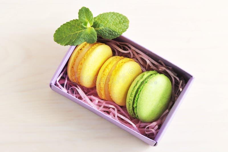 Macarons amarillos y verdes de la torta con la menta en caja en backgr de madera fotos de archivo