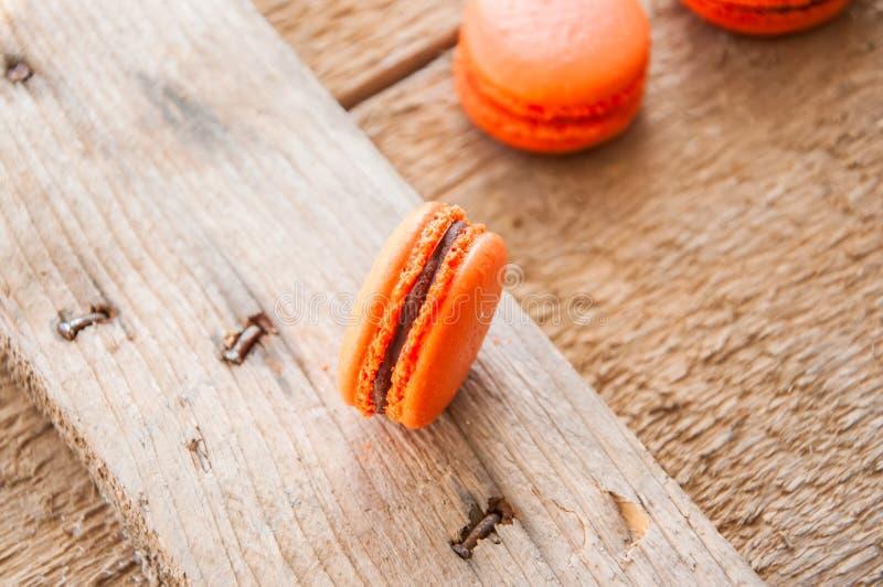 Macarons anaranjados con el relleno del ganache del chocolate fotografía de archivo libre de regalías