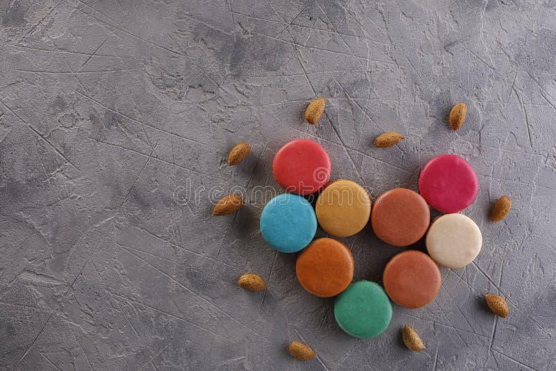 Macarons apresentou sob a forma das porcas do coração e da amêndoa em um fundo estrutural Configuração lisa Conceito da nutrição imagem de stock