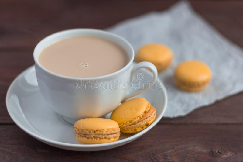 Macarons, biscuits d'amande délicieux et une tasse de café avec de la crème sur la table photographie stock