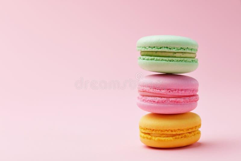 Macarons Bolinhos de amêndoa coloridos no fundo cor-de-rosa fotografia de stock