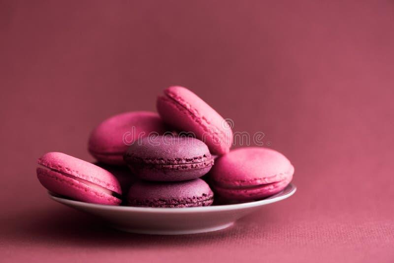 Macarons Bolinhos de am?ndoa franceses coloridos no fundo cor-de-rosa escuro Vida da sobremesa ou das cookies ainda fotografia de stock