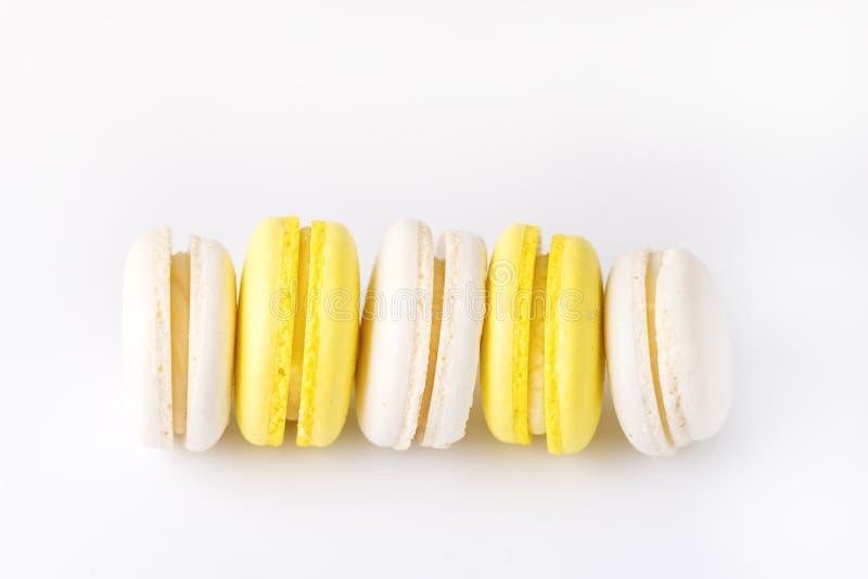 Macarons branco e amarelo de Macarons colorido francês na sobremesa branca do fundo imagens de stock royalty free