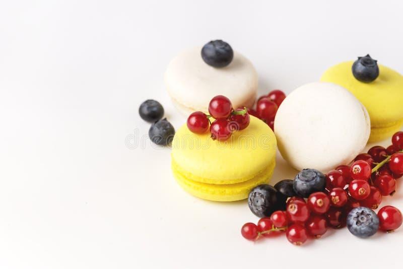 Macarons branco e amarelo de Macarons colorido francês no fundo azul com a sobremesa francesa horizontal do espaço fresco da cópi fotos de stock royalty free