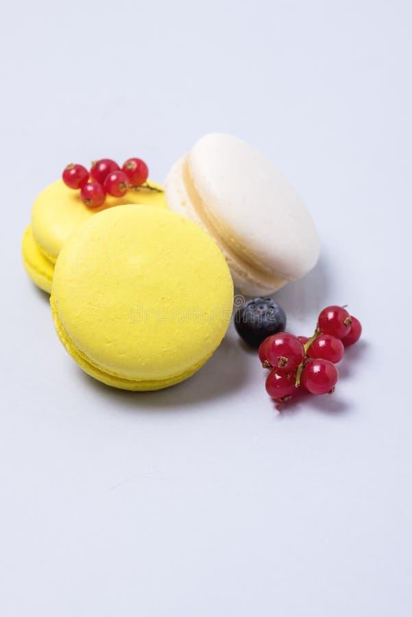 Macarons branco e amarelo de Macarons colorido francês no fundo azul com a sobremesa francesa vertical fresca do corinto vermelho imagem de stock