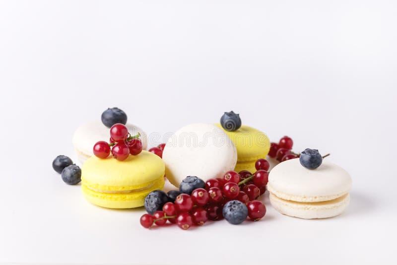 Macarons branco e amarelo de Macarons colorido francês no fundo branco com a sobremesa horizontal fresca do corinto vermelho e do imagens de stock royalty free