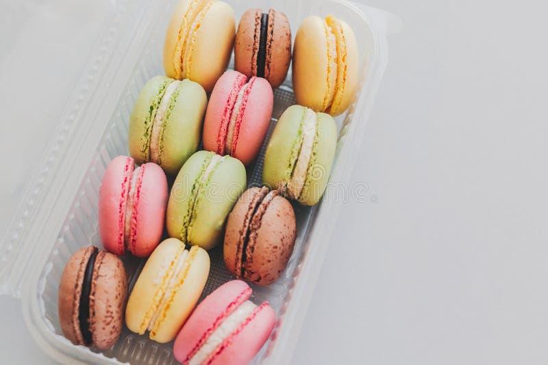 Macarons colorés délicieux dans la boîte en plastique sur le gra en pastel à la mode photo libre de droits