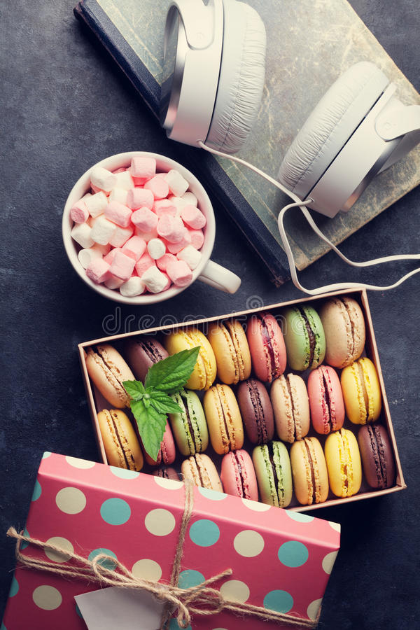 Macarons colorés dans un boîte-cadeau et des écouteurs photo libre de droits