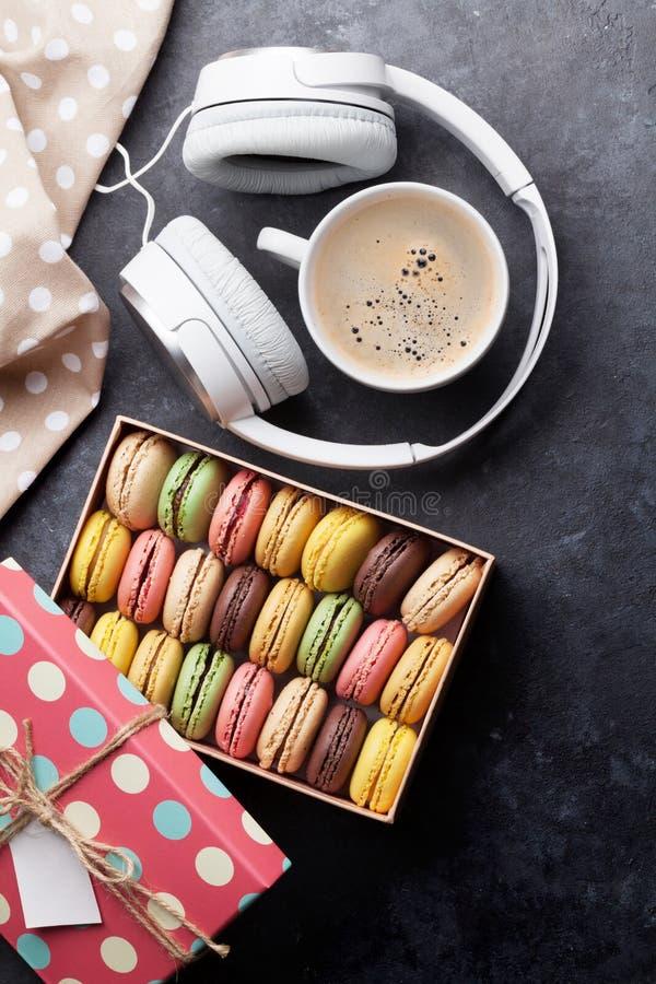 Macarons colorés dans un boîte-cadeau et des écouteurs image libre de droits