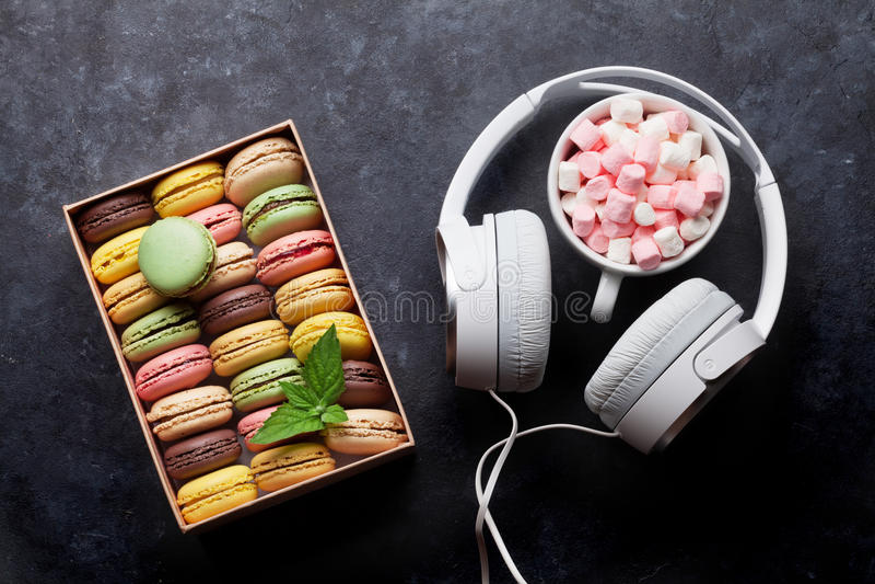 Macarons colorés dans un boîte-cadeau et des écouteurs photo stock
